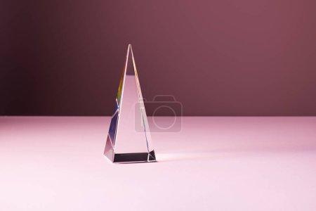 Photo pour Pyramide transparente cristal avec réflexion de la lumière sur fond rose - image libre de droit