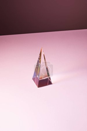 Photo for Crystal transparent pyramid with light reflection on pink background - Royalty Free Image