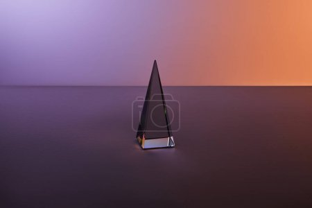 crystal transparent pyramid with light reflection on dark purple background