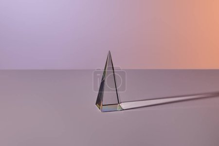Photo for Crystal transparent pyramid with light reflection on grey background - Royalty Free Image