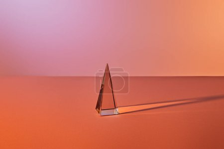 Photo for Crystal transparent pyramid with light reflection on orange background - Royalty Free Image