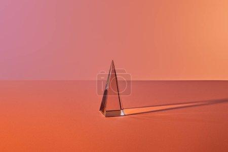 Photo pour Pyramide transparente cristal avec réflexion de la lumière sur fond orange - image libre de droit
