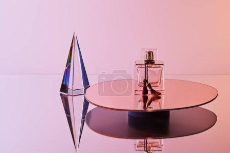Photo pour Pyramide transparente cristal avec reflet près du flacon de parfum sur miroir rond sur fond rose - image libre de droit