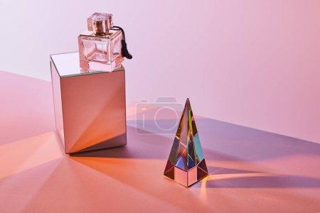 Photo pour Pyramide transparente cristal près bouteille de parfum sur cube sur fond rose - image libre de droit