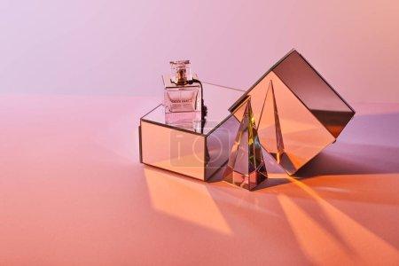 Photo pour Pyramide transparente cristal près du flacon de parfum et cubes miroir sur fond rose - image libre de droit