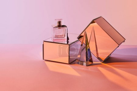 Photo for Crystal transparent pyramid near perfume bottle and mirror cubes on pink background - Royalty Free Image