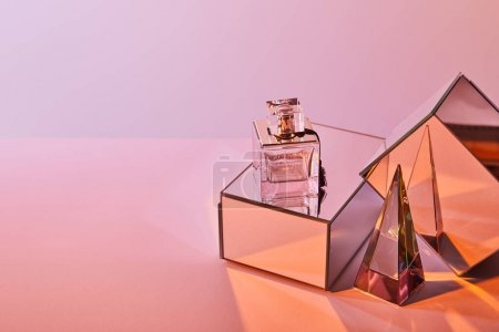 Photo pour Crystal transparent pyramide près de la bouteille de parfum et cubes miroirs sur fond rose - image libre de droit