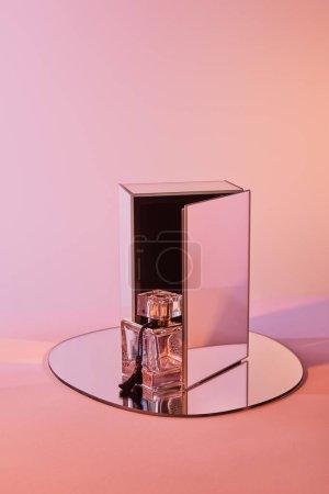 Photo pour Flacon de parfum sur miroir rond avec cube sur fond rose - image libre de droit
