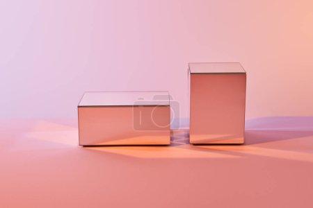 Foto de Cubos con reflejo de luz en la superficie sobre fondo rosa - Imagen libre de derechos