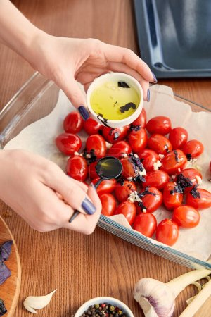 Photo for Cropped view of woman adding olive oil to tomatoes with ingredients near oven tray on wooden background - Royalty Free Image
