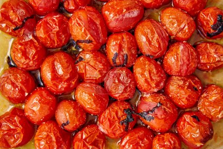 Photo for Top view of cooked tomatoes with cut basil leaves on baking paper - Royalty Free Image