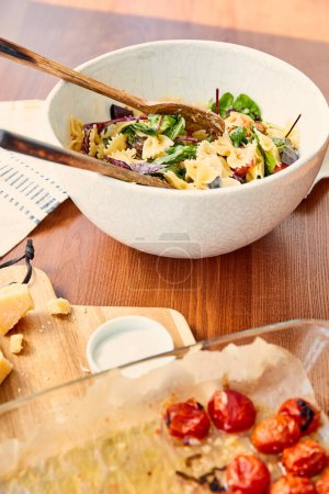 High angle view of bowl with pasta salad and ingredients on cutting board near napkin on wooden background