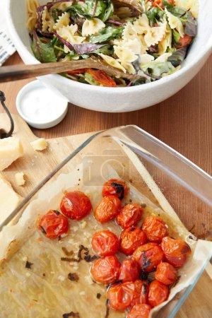Photo pour Vue grand angle du bol avec salade de pâtes près des ingrédients sur planche à découper et sel sur fond en bois - image libre de droit