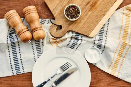 Teller mit Gabel und Messer in der Nähe von Serviette, Schneidebrett, Schüsseln, Pfeffer- und Salzmühlen auf Holzgrund