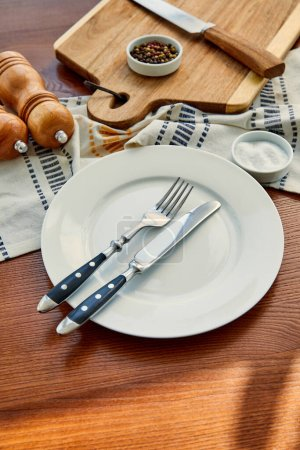 High angle view of plate with cutlery near napkin, cutting board, bowls, pepper and salt mills on wooden background