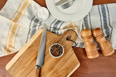 Photo for Top view of plate with cutlery near cloth, cutting board, bowls, pepper and salt mills on wooden background - Royalty Free Image
