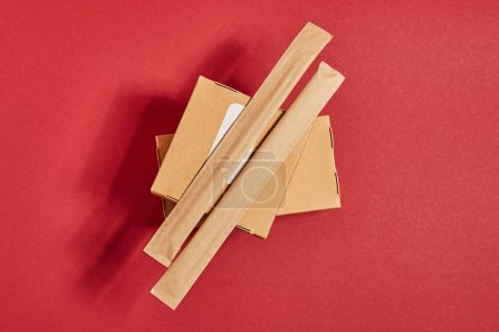 Photo for Top view of chopsticks in paper packaging on carton boxes with chinese food on red - Royalty Free Image