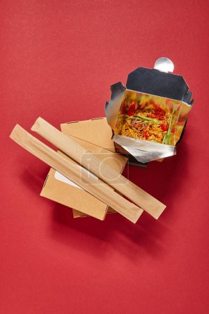 Photo for Top view of chopsticks in paper packaging near spicy noodles in takeaway box on red - Royalty Free Image
