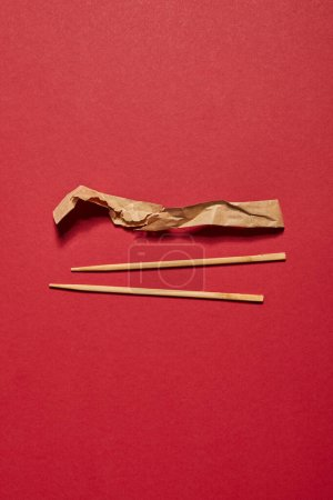 top view of wooden chopsticks near paper on red