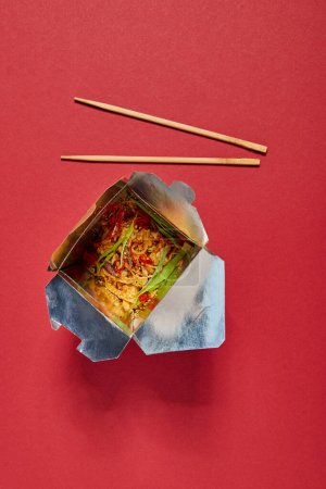 Photo for Top view of chopsticks near tasty noodles with vegetables in takeaway box on red - Royalty Free Image
