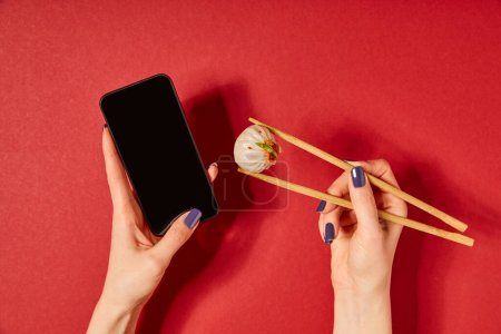 top view of woman holding chopsticks with steamed bun and smartphone with blank screen on red