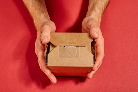 Photo for Cropped view of man holding carton takeaway box on red - Royalty Free Image