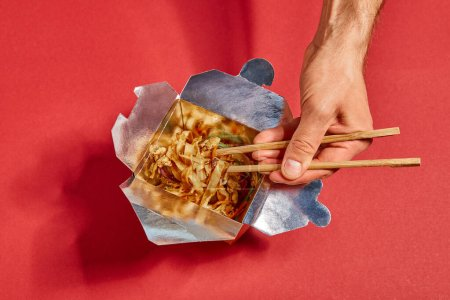 cropped view of man holding chopsticks near spicy noodles on red