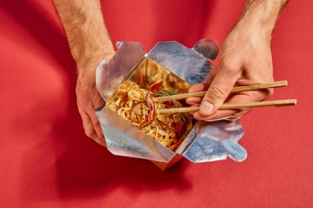 top view of man holding chopsticks near spicy noodles on red