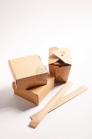 carton boxes with chinese food and chopsticks in packaging on white