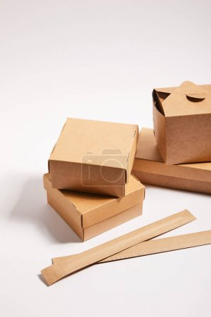 Photo for Chopsticks in paper packaging near carton boxes with chinese food on white - Royalty Free Image
