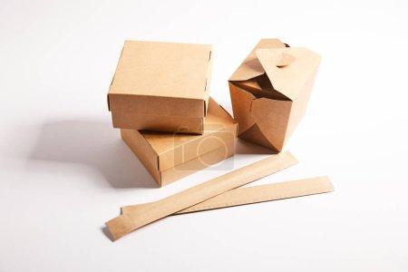 Essstäbchen in Papierverpackungen in der Nähe von Imbissboxen mit chinesischem Essen auf weißem Grund