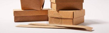 horizontales Bild von Essstäbchen in Papierverpackungen in der Nähe von Imbissbuden mit chinesischem Essen auf weißem Hintergrund