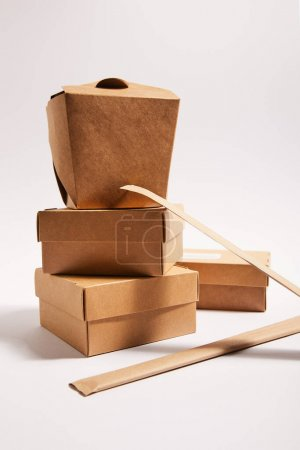 Photo for Chopsticks in paper packaging near takeaway carton boxes with traditional chinese food on white - Royalty Free Image