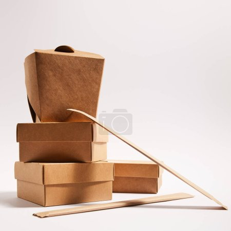 Photo for Chopsticks in paper packaging near takeaway boxes with prepared chinese food on white - Royalty Free Image