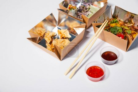 Photo for Sauces and chopsticks near takeaway boxes with prepared chinese food on white - Royalty Free Image
