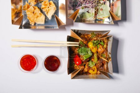 Photo for Top view of sauces and chopsticks near takeaway boxes with prepared chinese food on white - Royalty Free Image