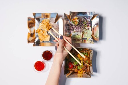 top view of woman holding chopsticks near takeaway boxes with prepared chinese food and sauces on white