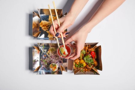 top view of woman holding chopsticks with dumpling and sauce near takeaway boxes with prepared chinese food on white