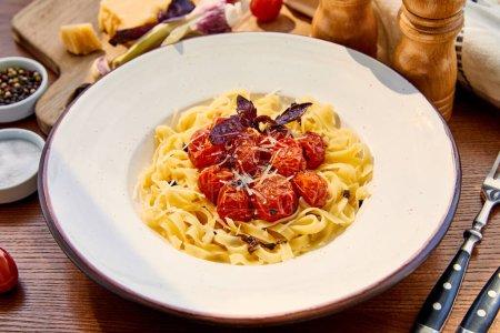 Photo pour Délicieuses pâtes aux tomates, basilic et parmesan servies en assiette ronde sur table en bois au soleil - image libre de droit
