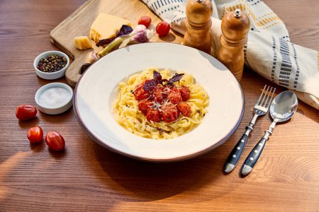 delicious pasta with tomatoes served on wooden table with cutlery, napkin, seasoning and ingredients in sunlight