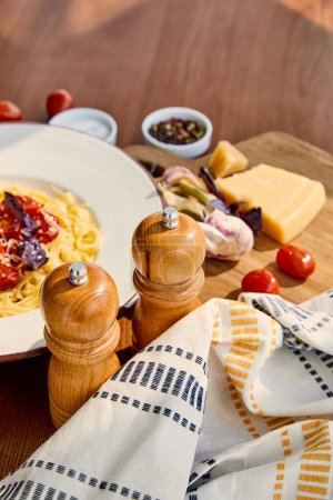 Photo for Selective focus of delicious pasta with tomatoes served on wooden table with cutlery, napkin, seasoning and ingredients in sunlight - Royalty Free Image