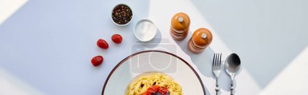 Photo for Top view of delicious pasta with tomatoes served with cutlery, salt and pepper mills on white table in sunlight, panoramic crop - Royalty Free Image