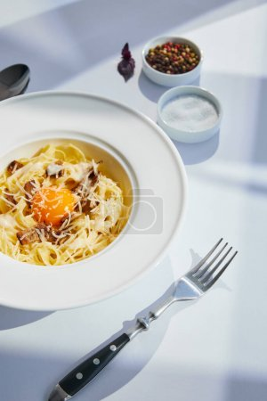 Photo for Delicious pasta carbonara served with cutlery and seasoning on white table in sunlight - Royalty Free Image