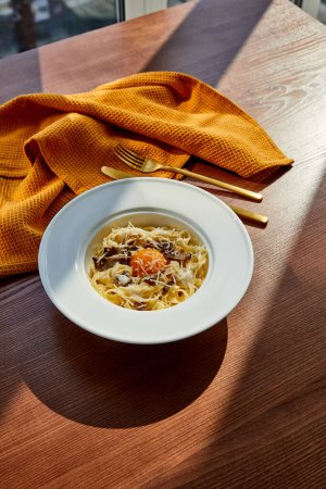 Photo for Delicious pasta carbonara served with golden cutlery and yellow napkin on wooden table in sunlight - Royalty Free Image
