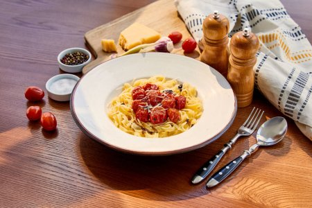 Photo for Delicious pasta with tomatoes served on wooden table with cutlery, napkin, seasoning and ingredients in sunlight - Royalty Free Image