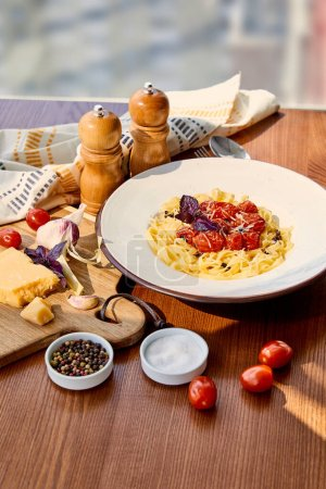delicious pasta with tomatoes served on wooden table with napkin, seasoning and ingredients in sunlight