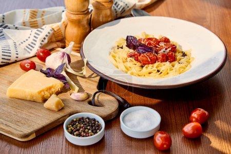 Photo pour Délicieuses pâtes aux tomates serviettes en bois, assaisonnement et ingrédients au soleil - image libre de droit