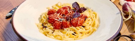delicious pasta with tomatoes, parmesan and red basil served on wooden table in sunlight, panoramic shot