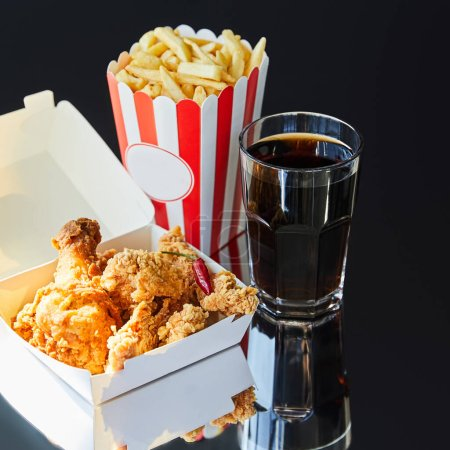 deep fried chicken, french fries and soda in glass on glass table