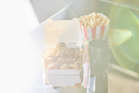 Photo for Deep fried chicken, french fries and soda in glass on glass table in sunlight - Royalty Free Image